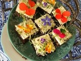 Pumpernickel sandwiches with herb cream cheese and edible flowers