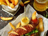Sausages With Beer Pretzel Buns, Beer Braised Onions & Roasted Garlic Butter