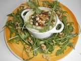 Eggs in a mini casserole dish with a roquefort cream, salad rocket and walnuts