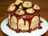 Triple layer chocolate cake coated in caramel butter cream, topped with salted caramel and decorated with chocolate dipped coconut macaroons